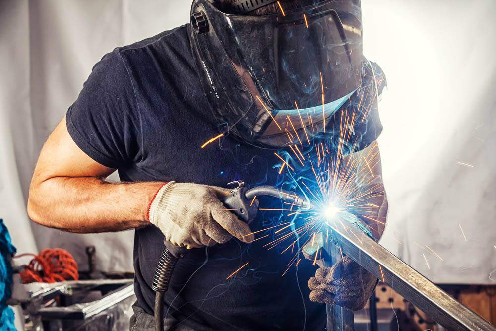 man weld a metal with a welding machine