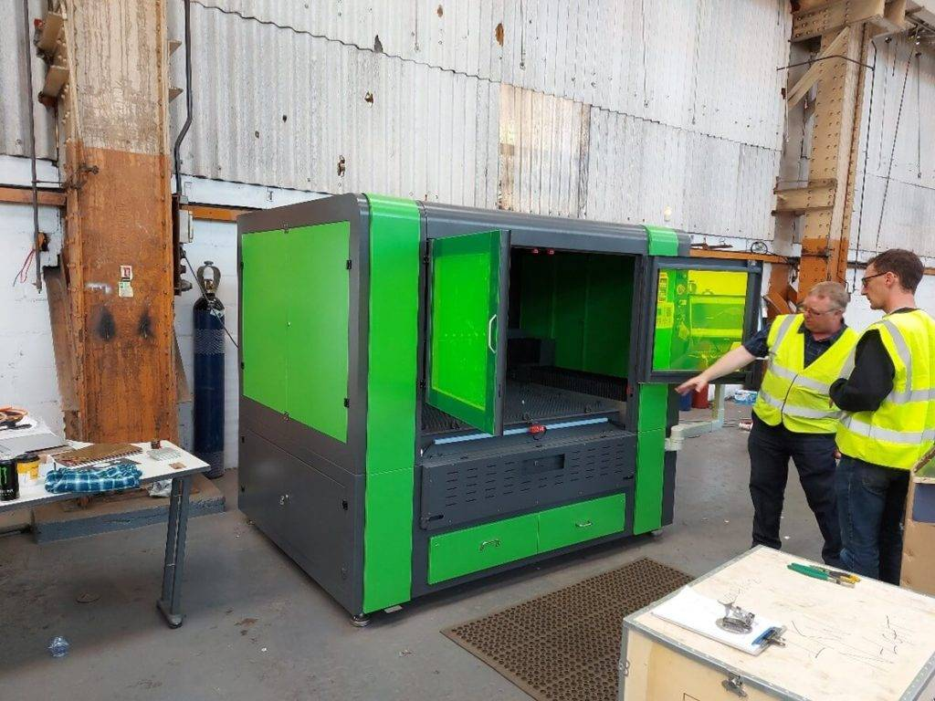 large laser cutting machine with people looking at it